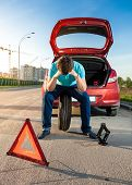 Sad Man Sitting On Spare Wheel Near Broken Car