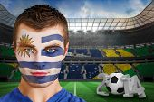 Composite image of serious young uruguay fan with facepaint against large football stadium