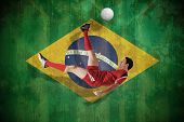 Football player in red kicking against brazil flag in grunge effect