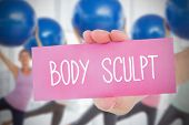 Woman holding pink card saying body sculpt against fitness class in gym