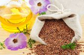 image of flax seed oil  - Macro view of flax seeds in flax sack and glass bottle of flax oil with flowers isolated on white background - JPG