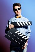 Extravagant young man holding clapper board. Cinema industry. Different occupations. Black-and-white photo.
