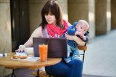Young Mother With Little Son Working On Her Laptop