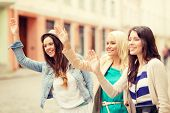 holidays and tourism concept - three beautiful girls waving hands in the city
