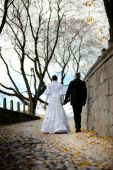 Bride And Groom Walking In An Autumn Park