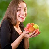 Young And Smiling Woman Holding A Bunch Of Colorful Macaroons On Green Blurred Background, Close-up