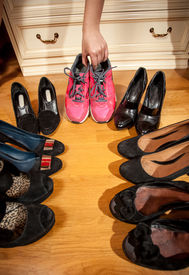stock photo of hughes  - Closeup photo of woman choosing sneakers rather than hugh heeled shoes - JPG