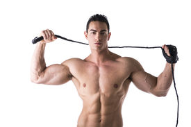 stock photo of strip tease  - Muscular shirtless young man with whip and studded glove on white background - JPG