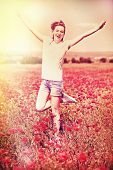 Beautiful young woman in poppy flowers field