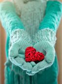 Female hands in light teal knitted mittens with entwined red heart . Winter and Christmas concept. St. Valentines day.