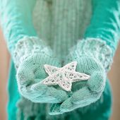 Female hands in light teal knitted mittens with entwined white star. Winter and Christmas concept.