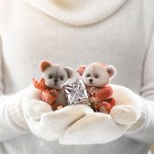 Little teddy bears in female hands in cozy mittens. Woman hands in white mittens holding a cute tiny teddy bear. Winter time and Christmas present concept.