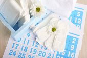 Sanitary pads in box and sanitary pads and white flowers on blue calendar on light grey background
