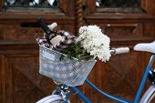 Old bicycle with flowers in metal basket on brown door background