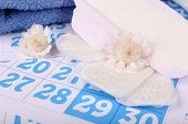 Sanitary pads, white flowers and towel on blue calendar background
