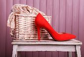 Red women shoes and scarf on bench on wooden background