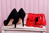 Black women shoes and beautician on wooden background