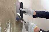 picture of putty  - Process putty concrete wall with a metal spatula - JPG