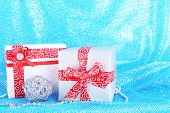 Holiday gift boxes decorated with red ribbon on blue fabric background