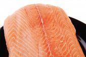 fresh raw salmon fillet on black over white