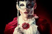 Handsome vampire wearing venetian mask. Halloween carnival. Dracula costume.