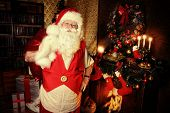 Santa Claus standing at home with gifts, dressed in his home clothes. Christmas. Decoration.