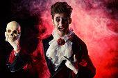 Comic vampire holding a skull. Halloween. Dracula costume.