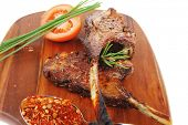 meat savory on wooden plate: roast ribs with peppers tomato and dry spices isolated on white