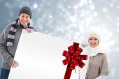 Winter couple showing poster with red christmas ribbon