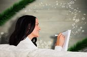Woman writing down some notes against blurred fir tree branches