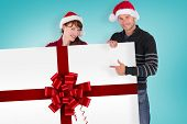 Couple holding a white sign against red christmas ribbon