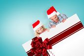 Young festive couple against red christmas ribbon