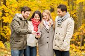vacation, people, technology and friendship concept - group of smiling friends with smartphone in autumn park