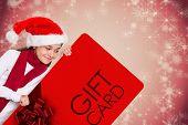 Festive little girl showing card against white snowflake design on red