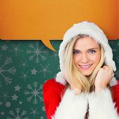 Pretty girl smiling in santa outfit against green vignette