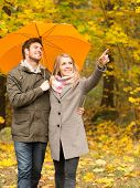 love, relationship, season, family and people concept - smiling couple with umbrella walking in autumn park