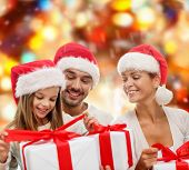 family, christmas, generation, holidays and people concept - happy family in santa helper hats with gift boxes sitting over red lights background