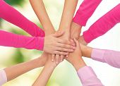 healthcare, people, gesture and medicine concept - close up of women hands on top of each other over green background