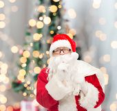 christmas, holidays and people concept - man in costume of santa claus with bag making hush gesture over tree lights background