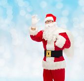 christmas, holidays, gesture and people concept - man in costume of santa claus with bag waving hand over blue lights background