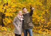 love, relationship, family and people concept - smiling couple hugging and pointing finger in autumn park