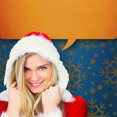 Pretty girl smiling in santa outfit against blue vignette