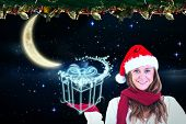 Festive blonde presenting with hand against crescent moon in the night sky
