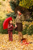 woman and little girl in autumn park with apple basket and umbrella