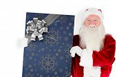 Santa claus showing blackboard against christmas wrapping paper with bow
