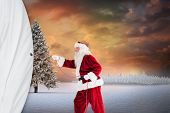 Santa pulls something with a rope against fir tree in snowy landscape