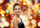 people, winter holidays, christmas and glamour concept - smiling woman in evening dress over red lights background