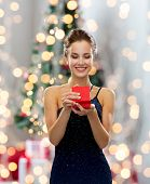holidays, celebration and people concept - smiling woman in dress holding red gift box over christmas tree lights background