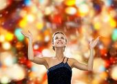people, happiness, holidays and glamour concept - smiling woman raising hands and looking up over red lights background