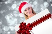 Festive blonde smiling at camera against red christmas ribbon